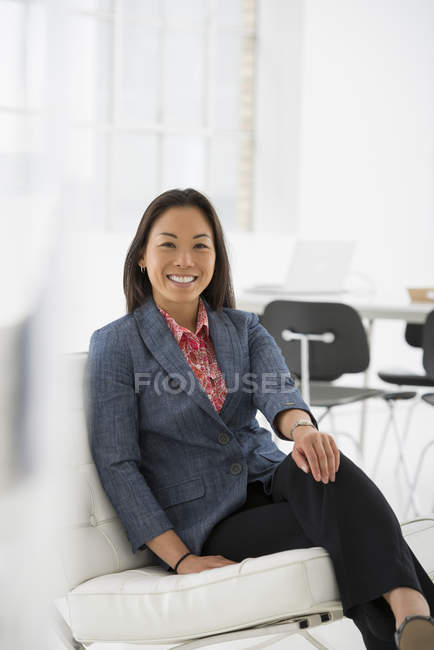 Woman relaxing on comfortable chair in modern office interior. — Stock Photo