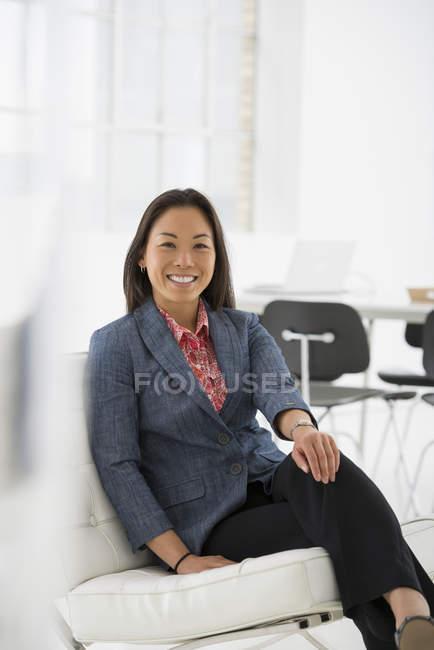 Mulher, relaxante na cadeira confortável no interior do escritório moderno — Fotografia de Stock