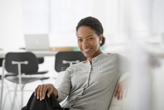 Mulher, relaxante na cadeira confortável no interior do escritório moderno. — Fotografia de Stock