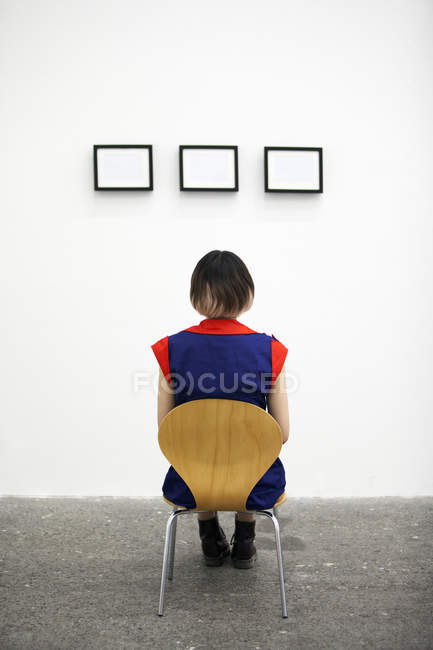 Rear view of woman sitting on chair and looking at artwork in gallery. — Stock Photo