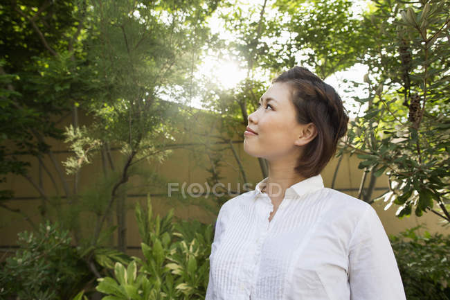 Young Asian woman looking up and enjoying trees of city park. — Stock Photo