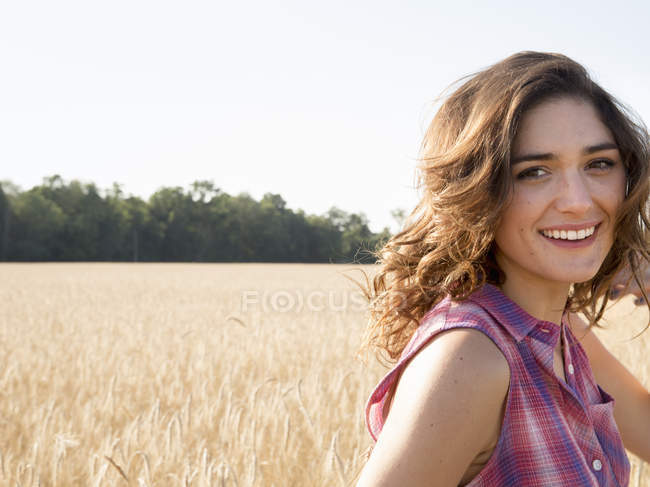Young woman standing in cornfield, smiling and looking in camera. — Stock Photo
