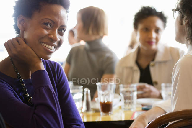 African american woman sitting with hand on chin in bar with friends. — Stock Photo