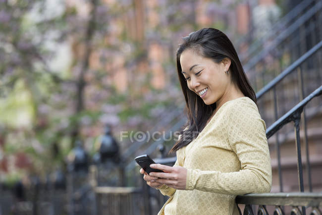 Asian woman leaning on railing on city street and using smartphone. — Stock Photo