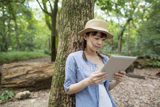 Giovane donna che utilizza tablet digitale nella foresta soleggiata . — Foto stock