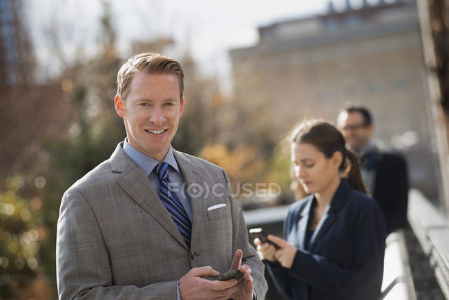 Group of people standing on street with mobile phones in New York, USA. — Stock Photo