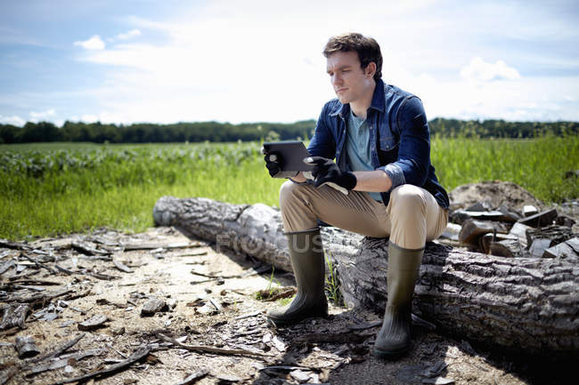 Farmer sitting on log at organic corn farm field and using digital tablet. — Stock Photo