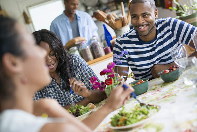 Group of friends sharing dinner in country kitchen interior. — Stock Photo