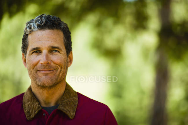 Head and shoulders of mature man looking in camera outdoors. — Stock Photo