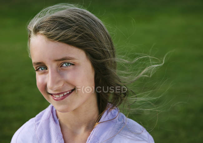 Portrait of smiling elementary age girl against green grass. — Stock Photo