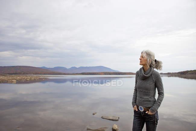 Reife Frau sucht entfernt am Ufer des herbstlichen See. — Stockfoto