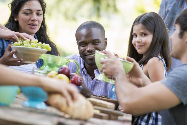 Amitié avec la fille d'âge élémentaire assis à une table en plein air dans le jardin avec des fruits et légumes. — Photo de stock