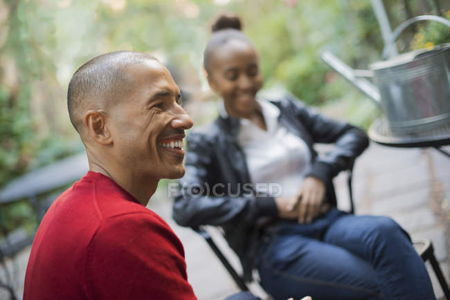 Mid adult man and teenage girl resting outdoors in chairs. — Stock Photo