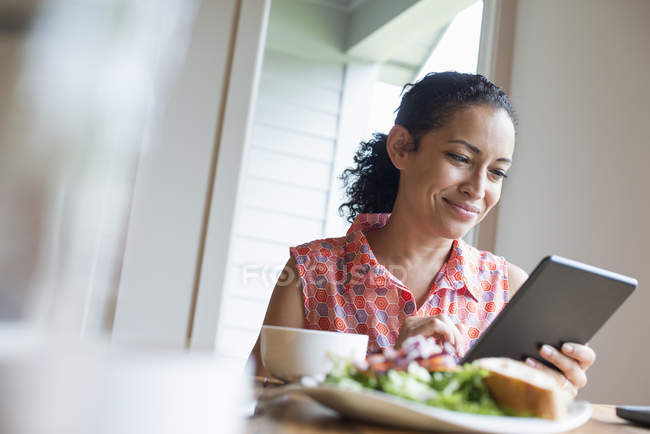 Woman smiling while using digital tablet at cafe table with coffee and sandwich. — Stock Photo