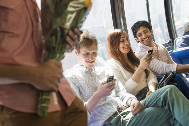 Group of people riding by city bus with smartphones and flowers. — Stock Photo