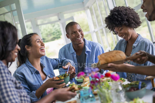 Group of women and men sharing dinner and laughing in country house interior. — Stock Photo