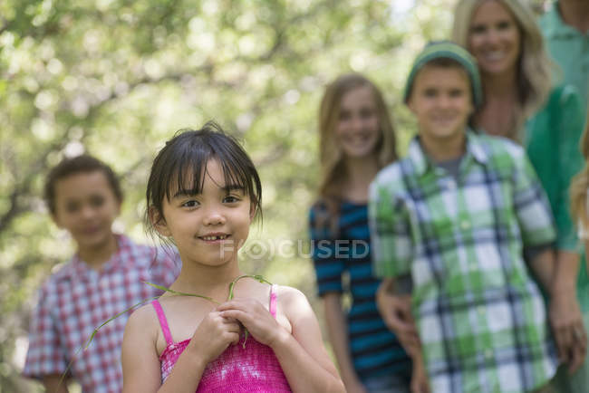 Elementary age girl and group of children and adults posing outdoors in garden. — Stock Photo