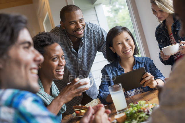 Group of people holding coffee cups and using digital tablet at meeting in cafe. — Stock Photo