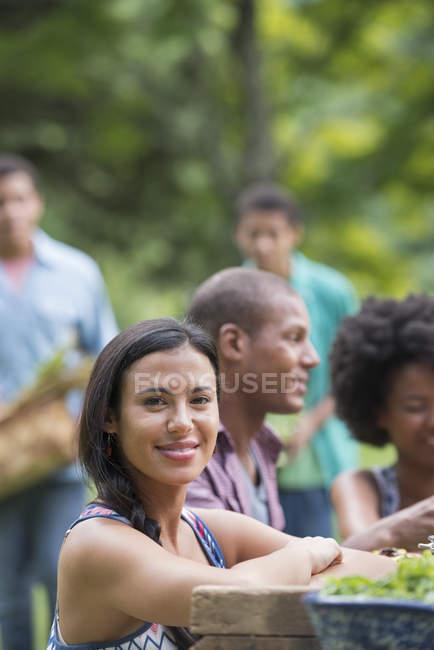 Junge Frau lächelt mit Freunden am Picknicktisch im Garten. — Stockfoto
