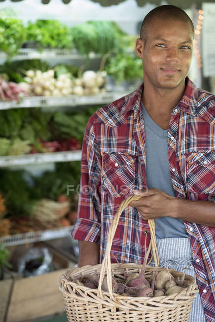 Man holding basket of organic vegetables at farmer store. — Stock Photo