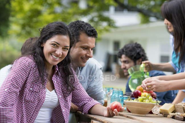 Femme adulte moyenne tenant pêche à la table extérieure avec des amis dans le jardin . — Photo de stock