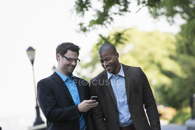 Hommes d'affaires marchant côte à côte sur la rue et regardant vers le bas à smartphone . — Photo de stock