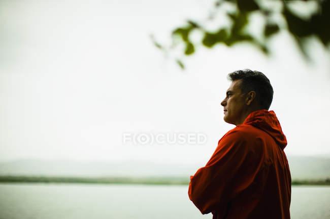 Зрелый человек в красной куртке, глядя на вид на загородную местность озера. — стоковое фото