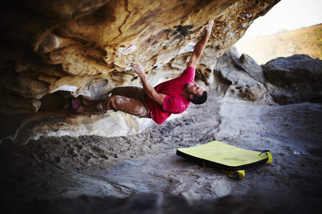 Man climbing on overhang of rock-face with minimum equipment. — Stock Photo