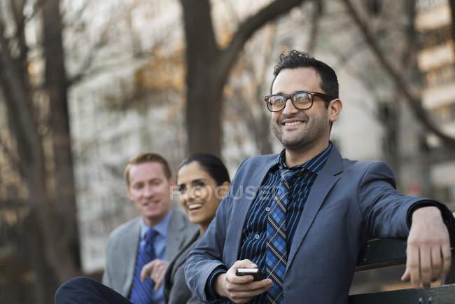 Бизнесмен, держащий смартфон с коллегами, отдыхающими на скамейке в городском парке . — стоковое фото