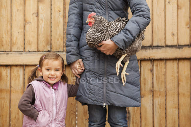 Woman in grey coat holding black and white chicken and holding hands with girl. — Stock Photo