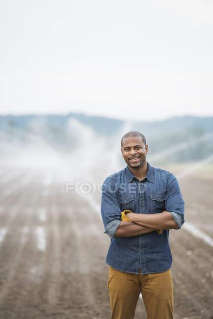 Молоді чоловіки фермер в робочий одяг на органічні поля з Зрошувальні води спринклери. — стокове фото