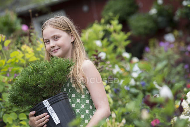 Pre-adolescent girl carrying green plant in pot in organic plant nursery. — Stock Photo