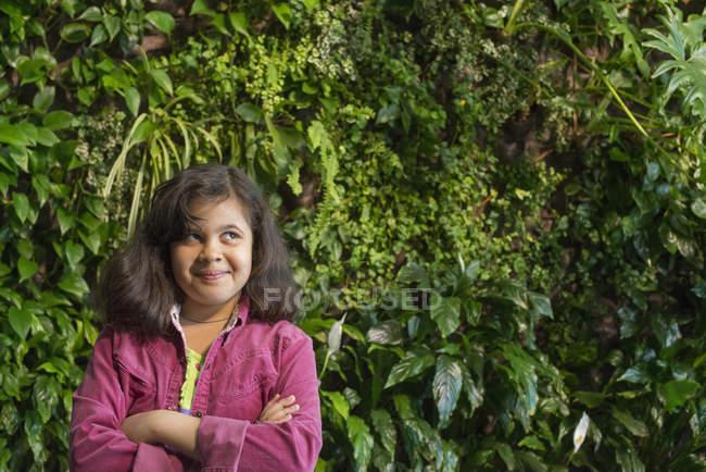 Девушка, стоящая перед стеной, покрытая папоротниками и альпинистскими растениями . — стоковое фото