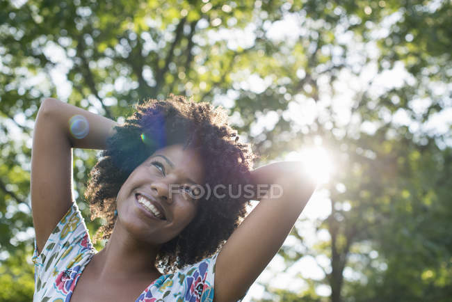 Young woman in flowered dress with hands on head, smiling and looking up in sunny forest. — Stock Photo