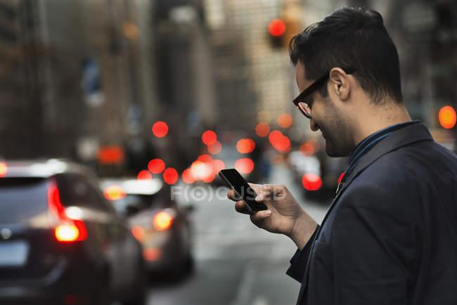 Hombre comprobar teléfono inteligente en la calle ocupada en la ciudad . - foto de stock