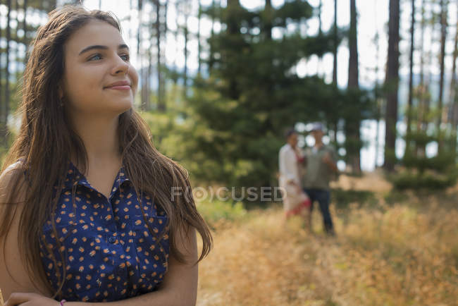 Young woman standing in woodland beside lake with people in background. — Stock Photo
