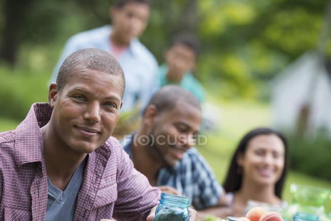 Молодой человек смотрит в камеру с друзьями за столом для пикника в сельском саду . — стоковое фото
