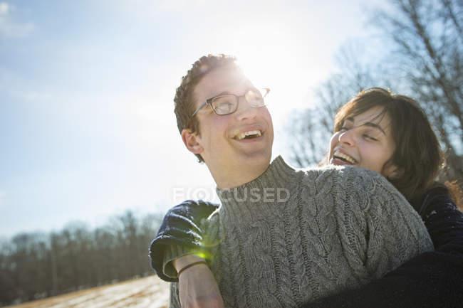 Homme et une femme étreignant et rire dans la forêt hivernale — Photo de stock