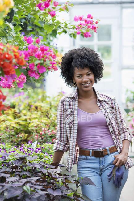 Жінка, стоячи в оточенні квіткових рослин і зеленого листя розплідники заводі — стокове фото