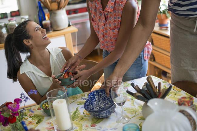 Femme riant et levant les yeux avec des amis à l'intérieur de la cuisine de campagne . — Photo de stock