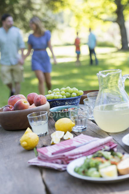 Served outdoor table with fruits and lemonade with people in background. — Stock Photo