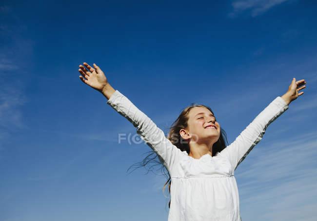 Portrait d'une fille d'âge élémentaire confiante avec les bras levés contre le ciel bleu — Photo de stock