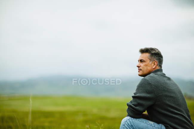 Hombre sentado y mirando hacia la distancia en prado verde niebla. - foto de stock