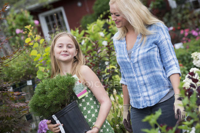 Woman and girl walking and carrying pot with green plants at organic plant nursery. — Stock Photo