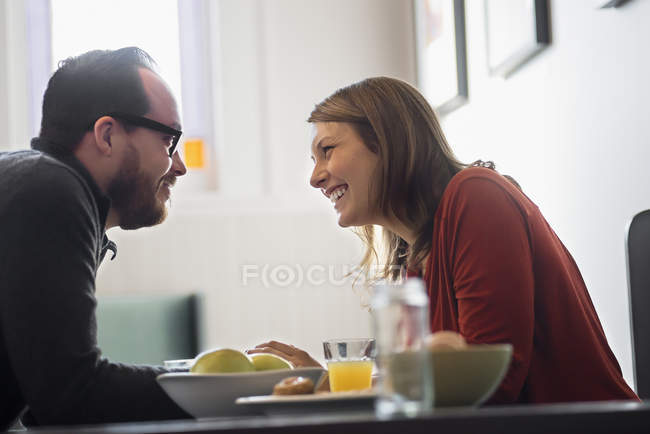 Couple leaning towards each other in coffee shop while breakfast. — Stockfoto