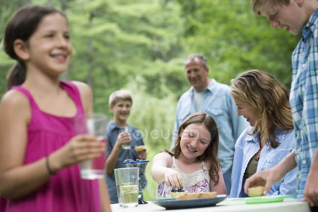 Famiglia con bambini pre-adolescenti avendo picnic all'aperto in giardino — Foto stock