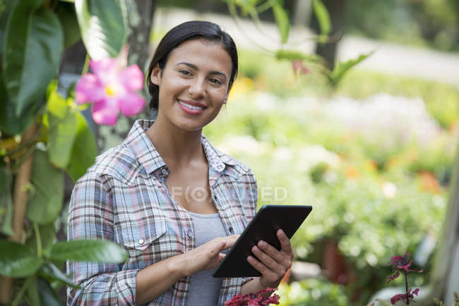 Young woman in organic nursery greenhouse using digital tablet. — Stock Photo