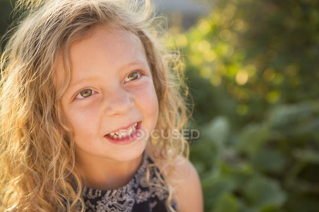 Ragazza in età elementare con i capelli ricci in giardino soleggiato . — Foto stock
