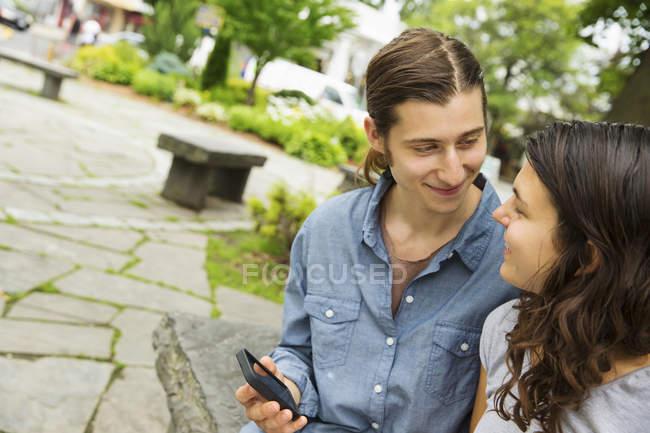 Junges paar nebeneinander sitzen, mit Blick auf einander und halten smartphone. — Stockfoto