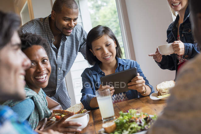 Group of people having lunch and using digital tablet at meeting in cafe. — Stock Photo